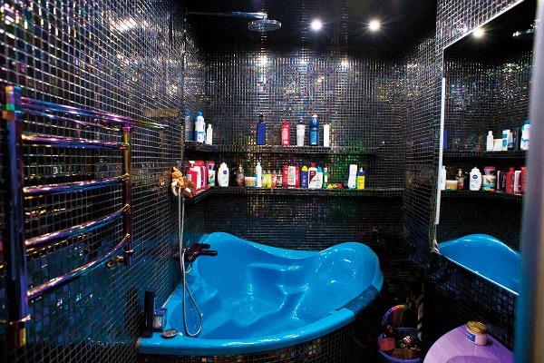 Ванная комната в отличие от всей квартиры оформлена в темных тонах
