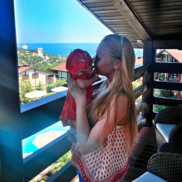 Дарья целует малыша на вернаде своего номера