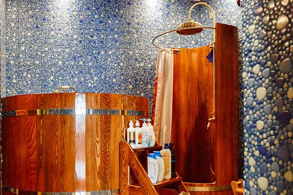 Интерьер ванной  оформлен под   русскую баню