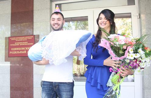 Александр и Алиана с новорожденным сыном на пороге роддома