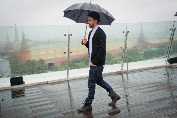 Певец вышел к фотографам и поклонникам всего на несколько минут, постарался улыбнуться, но довольно быстро вернулся под зонт и скрылся в теплом помещении