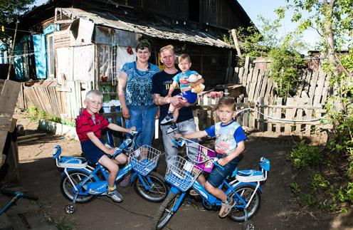 Настя с мужем и детьми – Колей, Сашей и Сергеем – во дворе своего дома. Чита, июнь 2014 года