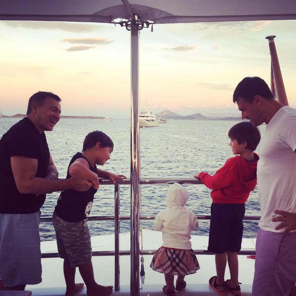 Эмин и его сыновья с умилением смотрят на малышку