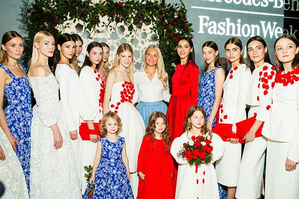 Милана Гогунская (в синем платье) и Яна Аршавина (с букетом цветов) в окружении взрослых моделей и дизайнера Юлии Прохоровой