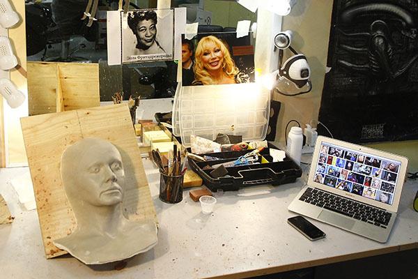 На рабочем столе гримера стоит слепок лица одного из участников, а на зеркале висят фотографии звезд, над образами которых предстоит работать