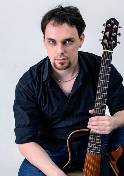 Мужчина играет на басу и поет в группе