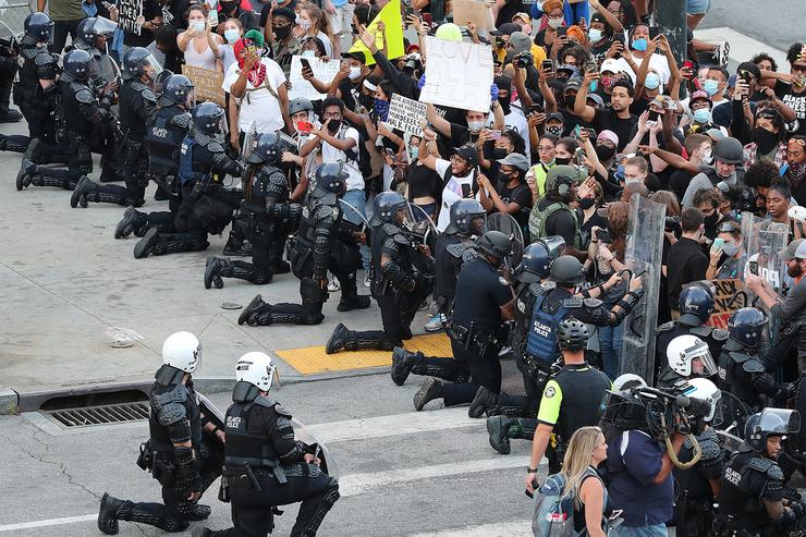 В знак мира и солидарности сотрудники правопорядка стоят на коленях перед протестующими, 1 июня 2020 года, штат Джорджия