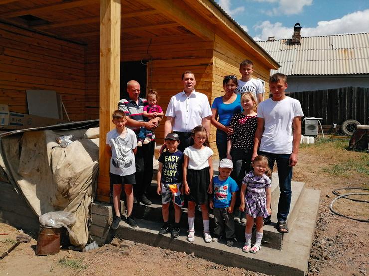 Супруги Поздняковы с детьми и мэром Игорем Шутенковым (в центре) на крыльце нового дома