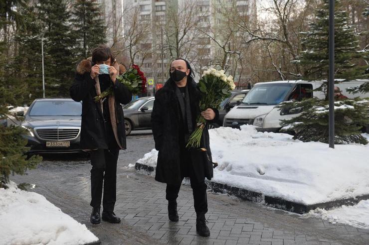 К гробу покойного несут букеты цветов