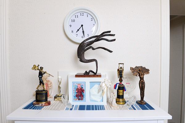 На комоде стоят награды Боб, фото сына, а также необычная металлическая статуэтка – подарок на свадьбу