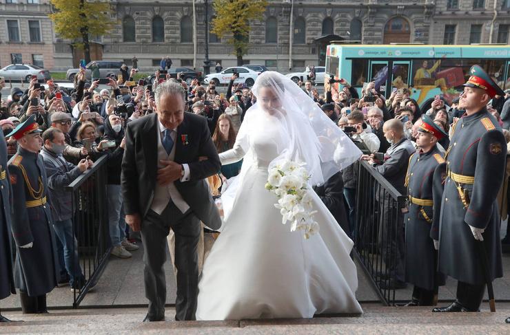Невеста вышла в платье с длинным шлейфом. Ее сопровождает отец Роберто Беттарини