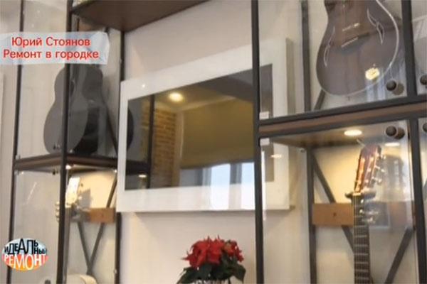 Между витринами с коллекцией гитар – телевизор в «волшебном зеркале»